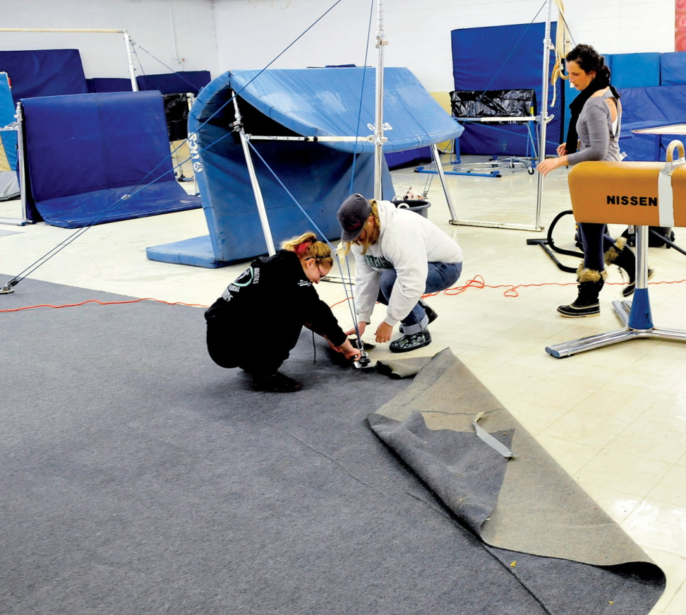 Staff photo by David Leaming RIPPING UP: Decal Gymnastics employees Whitney Blanchet, left, Kelli Hanson, center, and co-owner Delani Evans pull up carpet and other materials from the floor of the Farmington business on Tuesday. Water that poured in from the roof was discovered Monday evening damaging the spring floor, mats, carpets and foam pads.