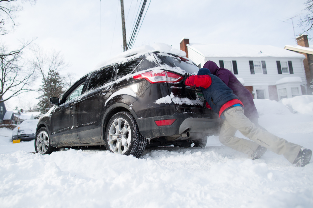 Will King, 14, tries to push an SUV driven by his father Bob up their driveway in Ann Arbor, Mich., on Monday.