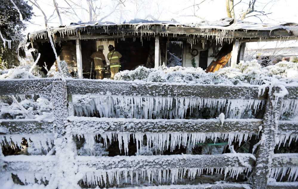 Lexington Fire Department Maj. Joe Madden, left, and firefighter Casey Wiley, look for hotspots at the scene of an overnight house fire in Lexington, Ky., Tuesday. Firefighters had to battle the fire in sub-zero temperatures.