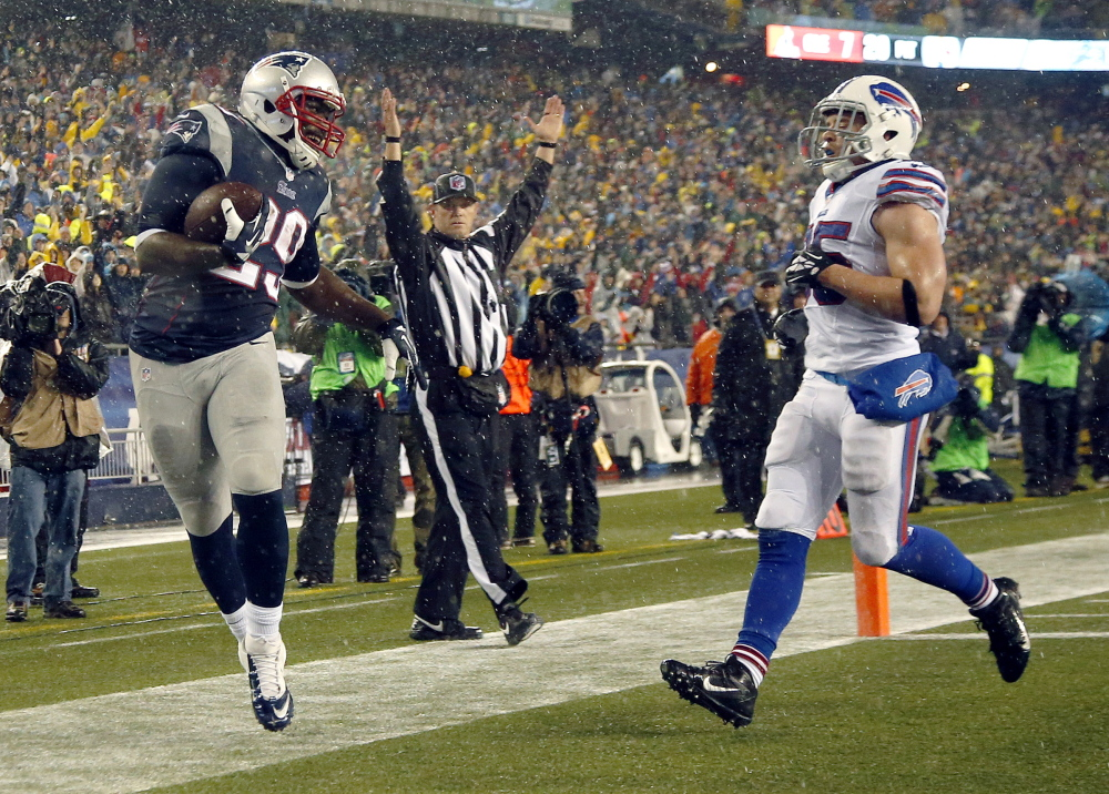 New England Patriots running back LeGarrette Blount (29) scores a touchdown past Buffalo Bills safety Jim Leonhard (35) in the second quarter of an NFL football game, Sunday, Dec. 29, 2013, in Foxborough, Mass.
