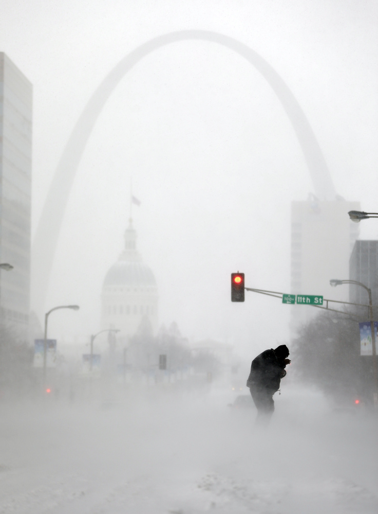 A person struggles to cross a street in St. Louis in blowing and falling snow on Sunday. Experts dismiss global warming skeptics who point to cold snaps as disproving climate change.
