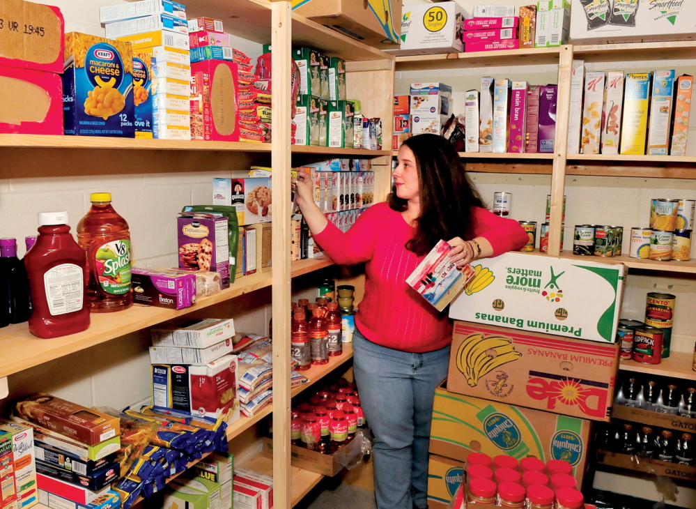 WELCOME: Jennifer Johnson stocks shelves in the recently opened food pantry at the Waterville's George J. Mitchell School, where 72 percent of children get free or reduced lunches.