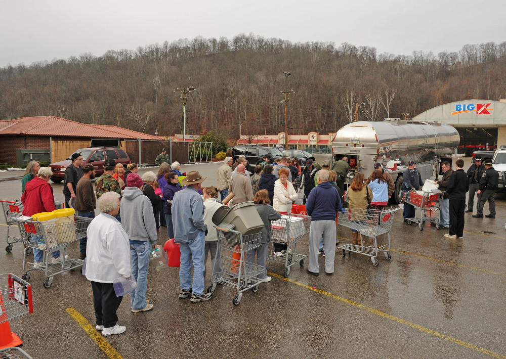 West Virginia state troopers fill water jugs at the Kmart in Elkview, W.Va., on Friday. Emergency crews are setting up water depots at many locations around the state following a chemical spill Thursday on the Elk River that compromised the public water supply to nine counties.