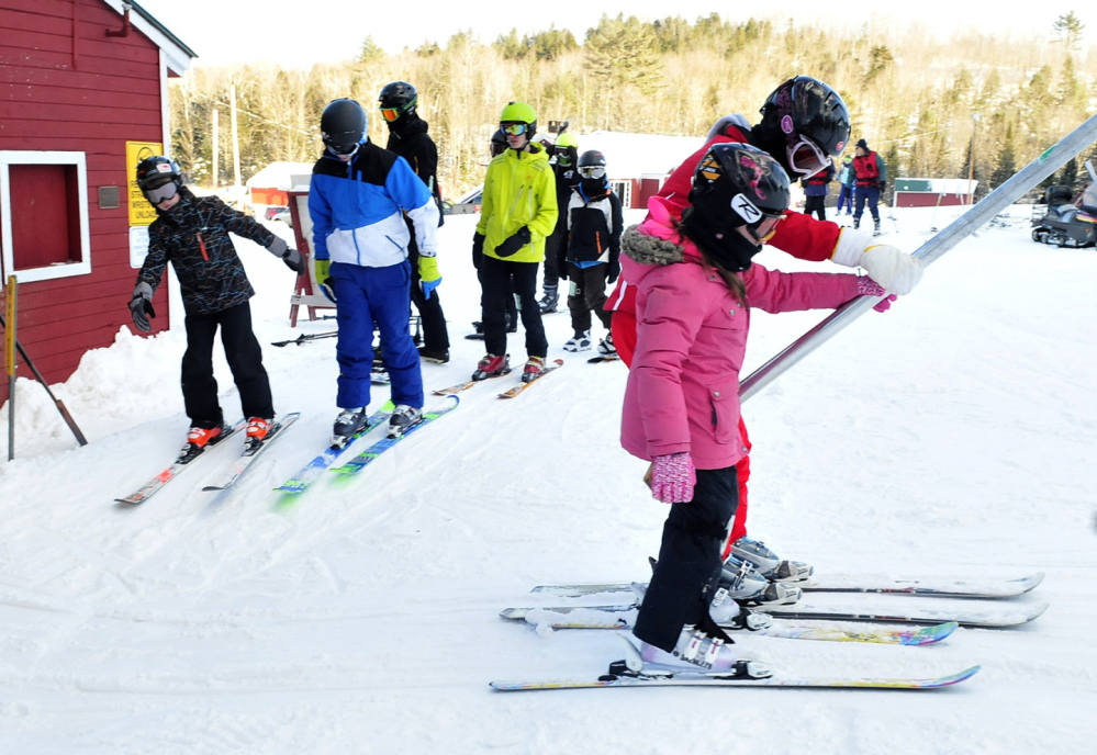 UPWARD: Skiers and snowboarders ride a T-bar lift at Titicomb Mountain Ski Area in Farmington.