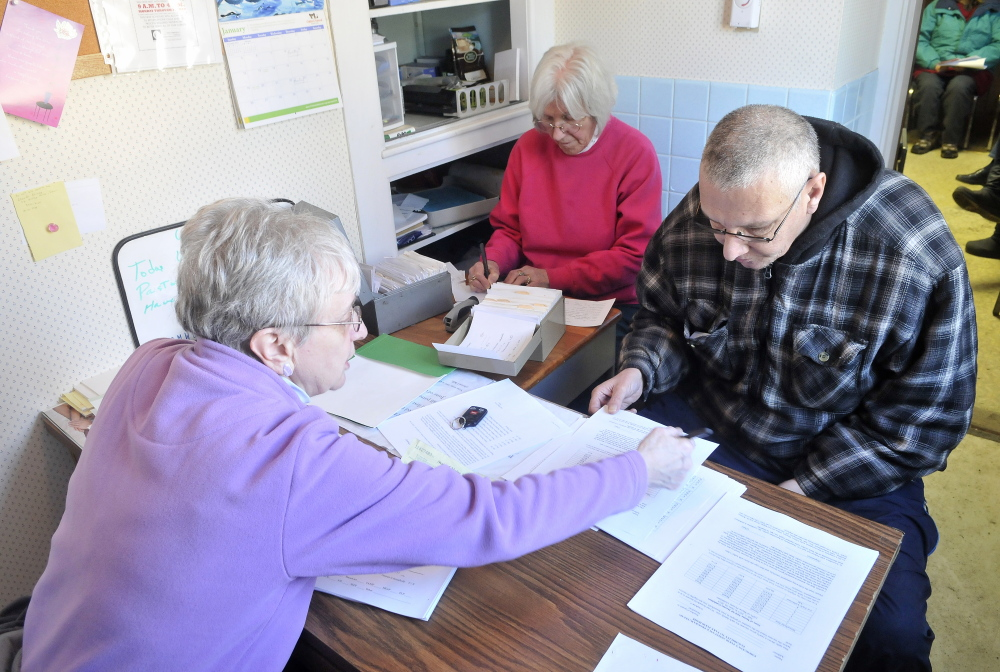 Paperwork: Pastor Joyce Perkins, left, helps Joe Lessard, 49, of Benton, fill out the proper paperwork to receive food from the First Baptist Church food pantry in Fairfield on Thursday.
