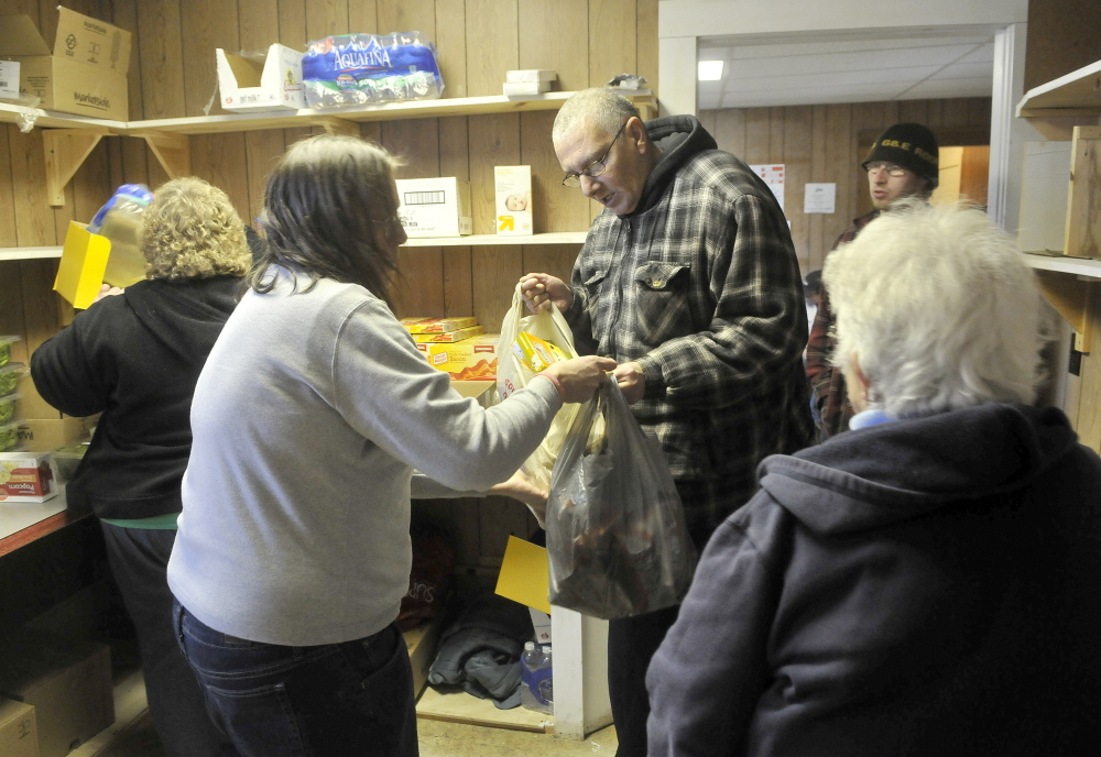 FOOD FOR FOLKS: Joe Lessard, 49, of Benton, center facing, receives bags of food from volunteers at the First Baptist Church food pantry in Fairfield on Thursday.