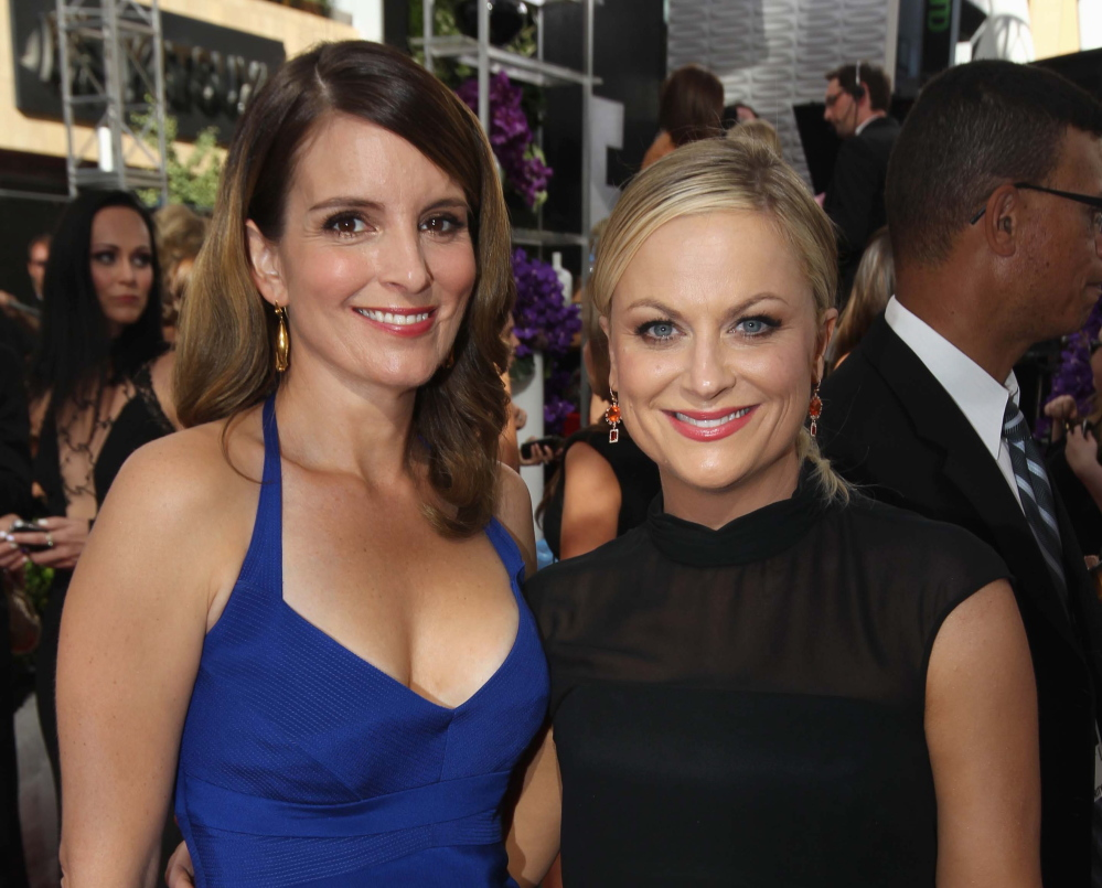Tina Fey, left, and Amy Poehler will again host the Golden Globes, where stars gather in a boozy dress rehearsal for the Oscars.