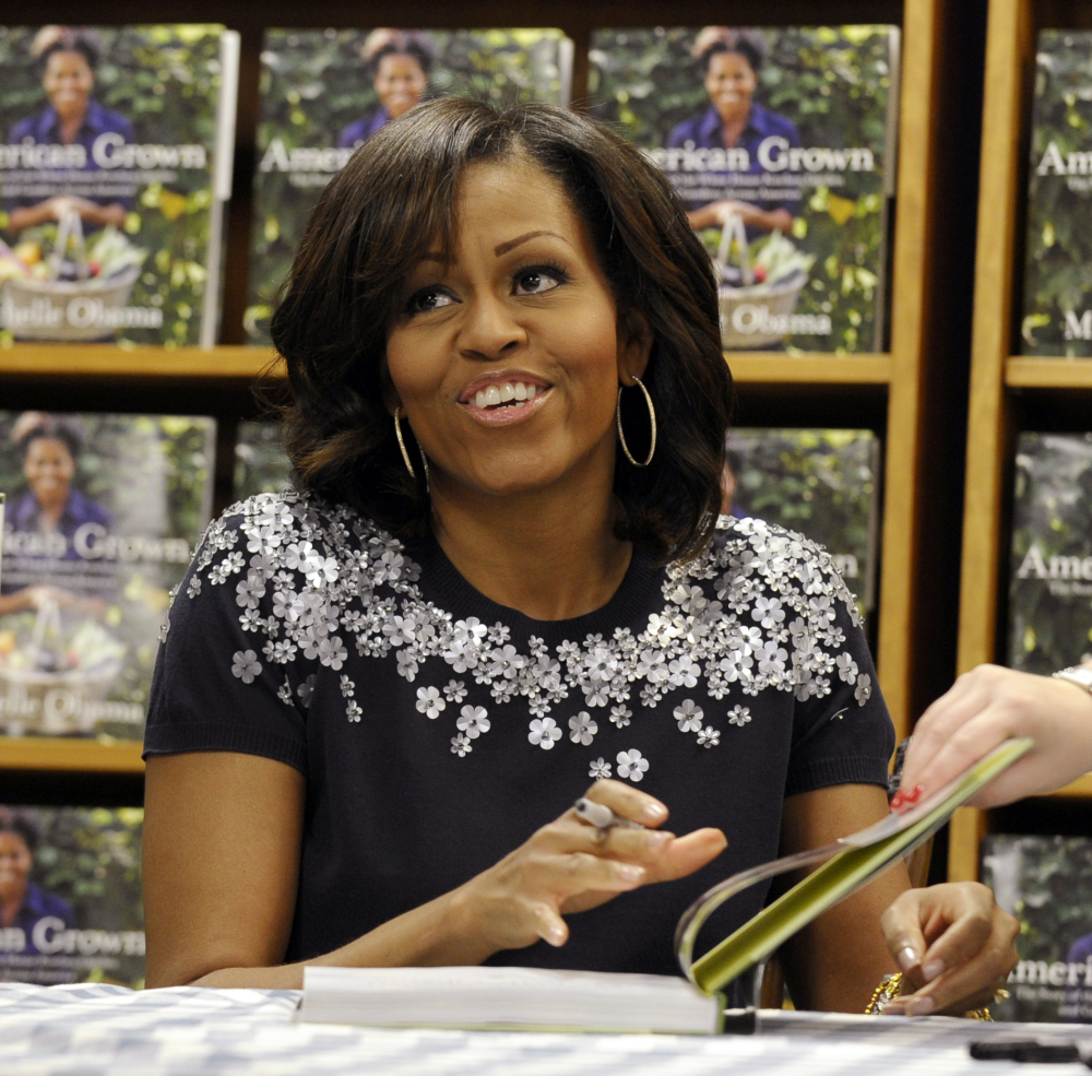 "Michelle Obama signs copies of her book, ""American Grown: The Story of the White House Kitchen Garden and Gardens Across America,"" at a bookstore in Washington in May. The nation's first lady turns 50 on Friday and, by her own account, feels more relaxed now that President Barack Obama's days as a candidate for elected office are over."