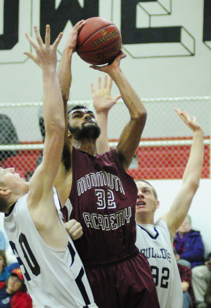 Staff photo by Joe Phelan Hall-Dale's Josh Berberich, left, and Wesley Lapointe, right, try to stop a shot by Monmouth Academy's Marcques Houston during a game on Wednesday January 15, 2014 in Hall-Dale's Penny Memorial Gym in Farmingdale.
