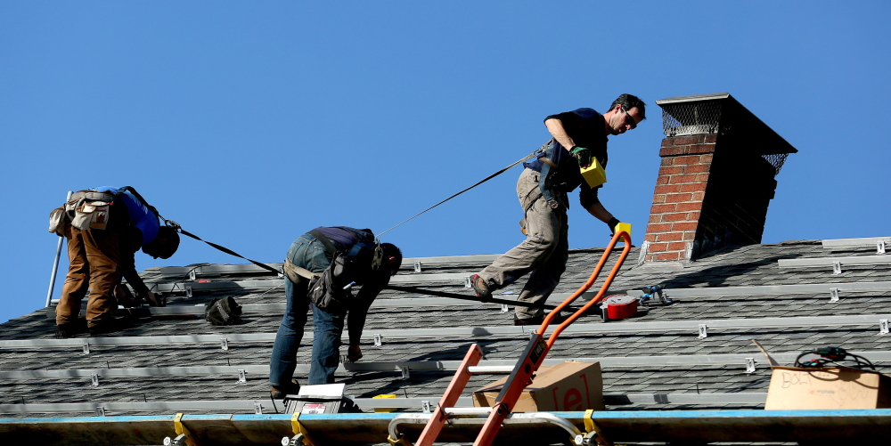 Matt Bush, Seth Kiernan and Brandon Bernard of ReVision Energy install support systems for solar panels on a house on Falmouth Road in Falmouth.