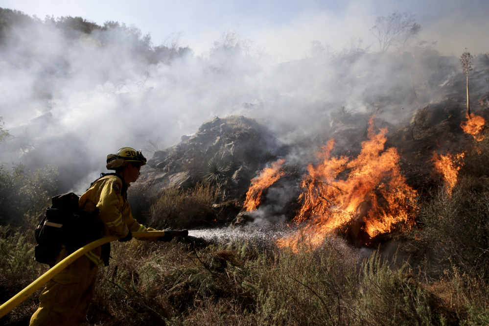 Firefighter Jeff Newby sprays water as he battles the Colby Fire near Azusa, Calif.