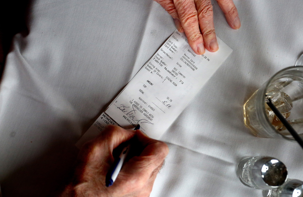 A patron signs his credit card receipt at DiMillo's. The IRS altered its tax code in 2012 to draw a distinction between voluntary tips and mandatory service charges.