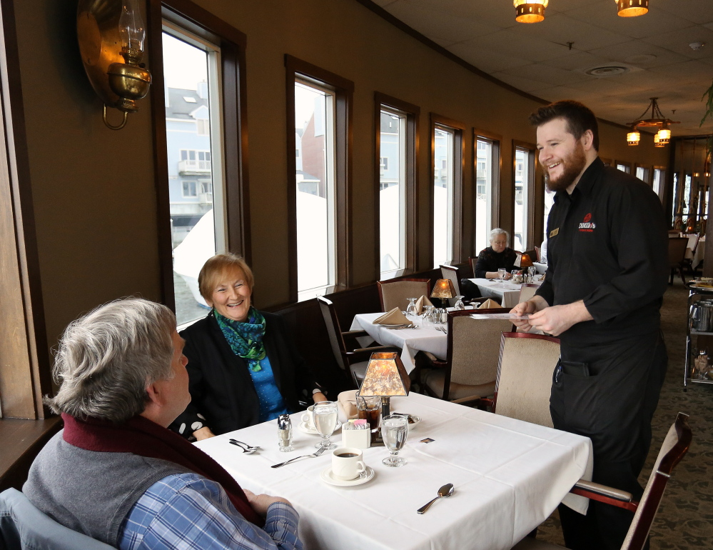 Adam Sousa, a server at DiMillo's Restaurant, takes the dessert order of Michael Kemna of Cumberland and Sherry Biegel of Gorham after lunch on Thursday. Sousa says he understands the reasoning behind dropping automatic gratuities, but he thinks waitstaff may suffer until guests in large parties become familiar with the need to tip.