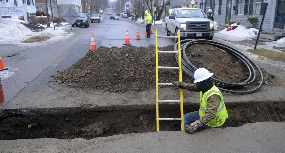 FILLING IN: A contractor installs a distribution line Thursday across Second Street in Hallowell for Summit Natural Gas of Maine. The 2013 arrival of two natural gas companies in the Kennebec Valley has strained the resources of communities and utilities. Summit was connecting a gas line to the building that houses the Liberal Cup.