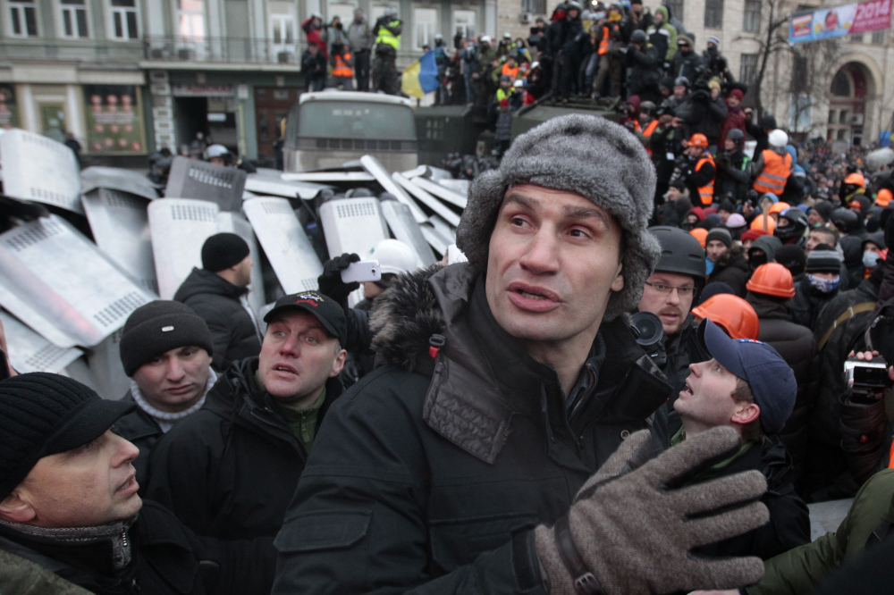 Opposition leader and former WBC heavyweight boxing champion Vitali Klitschko tries to stop the fighting between opposition protesters and riot police in Kiev, Ukraine, Sunday.