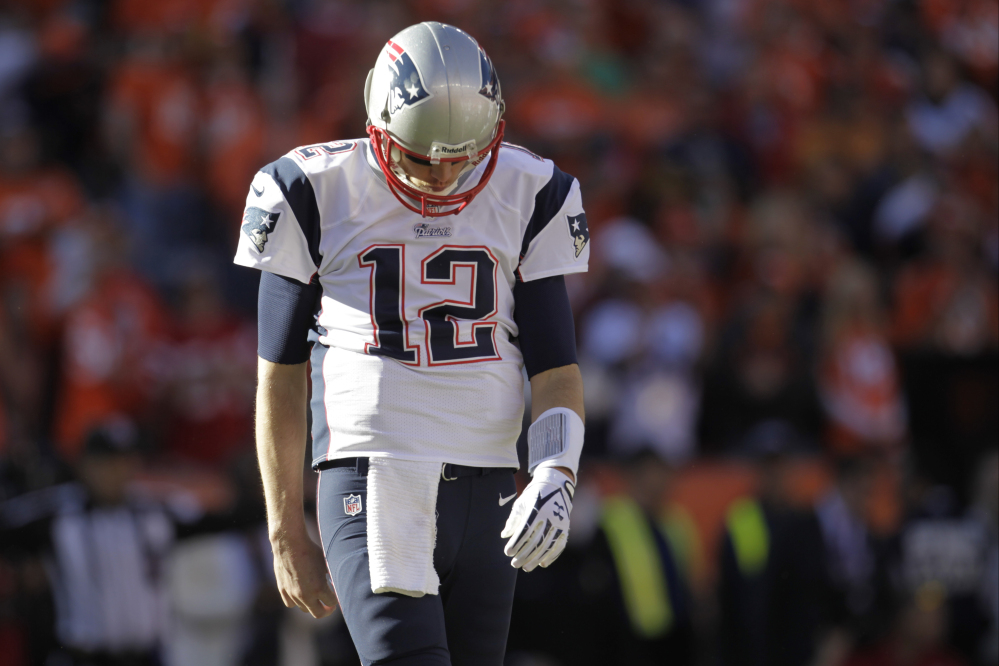 Patriots quarterback Tom Brady walks off the field after the first half of Sunday's AFC championship game at Denver.