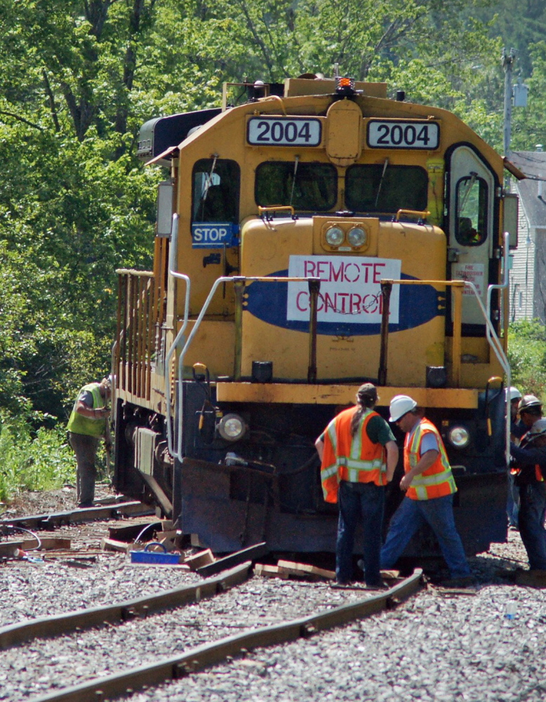 A crew from Montreal, Maine & Atlantic Railway repairs tracks in Brownville in July. The railway was auctioned Tuesday.