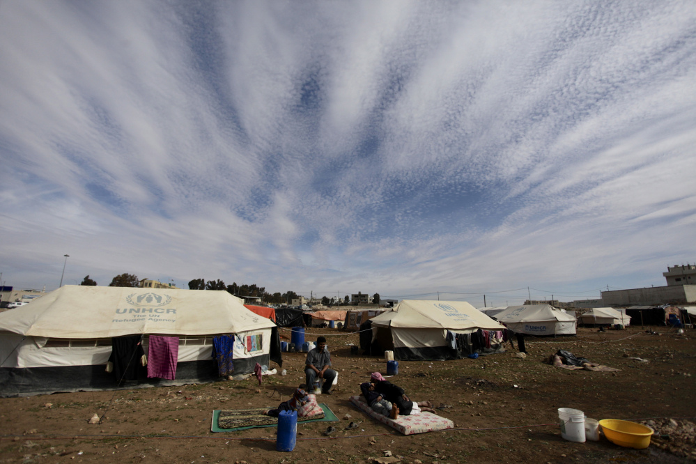 Refugees take a rest outside their tents at an unofficial refugee camp on the outskirts of Amman, Jordan, Wednesday, Jan. 22, 2014. Peace talks intended to carve a path out of Syria's civil war got off to a rocky start Wednesday.
