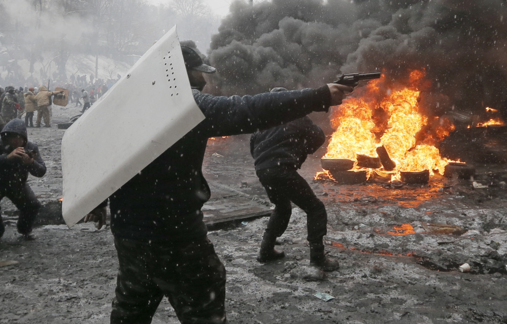 A protester points a handgun during a clash with police in central Kiev, Ukraine, Wednesday.