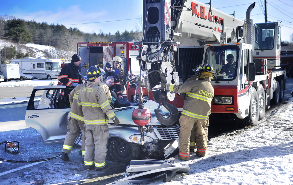 COLLISION: Firefighters and police work at extricating Sally Grouse of Chelsea, who was trapped in her car after pulling out of her driveway into the path of a crane Thursday afternoon on Route 9.