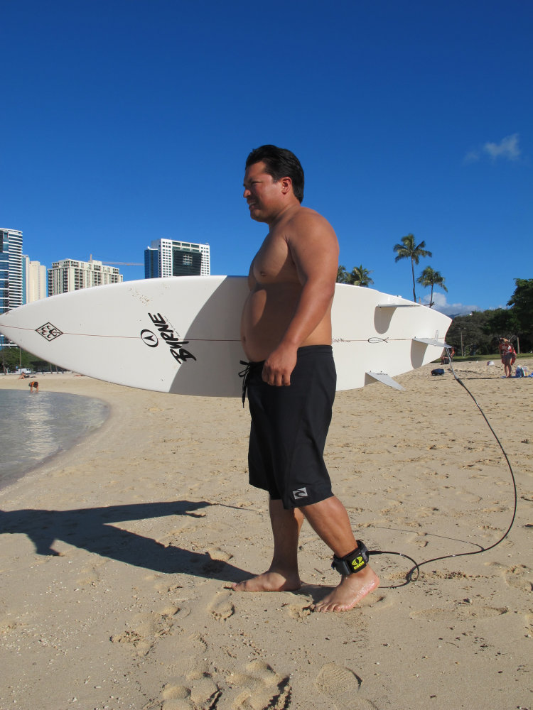 Rudy Aguilar models a shark deterrent device, the Electronic Shark Defense System, attached to his ankle and surfboard in Honolulu recently.