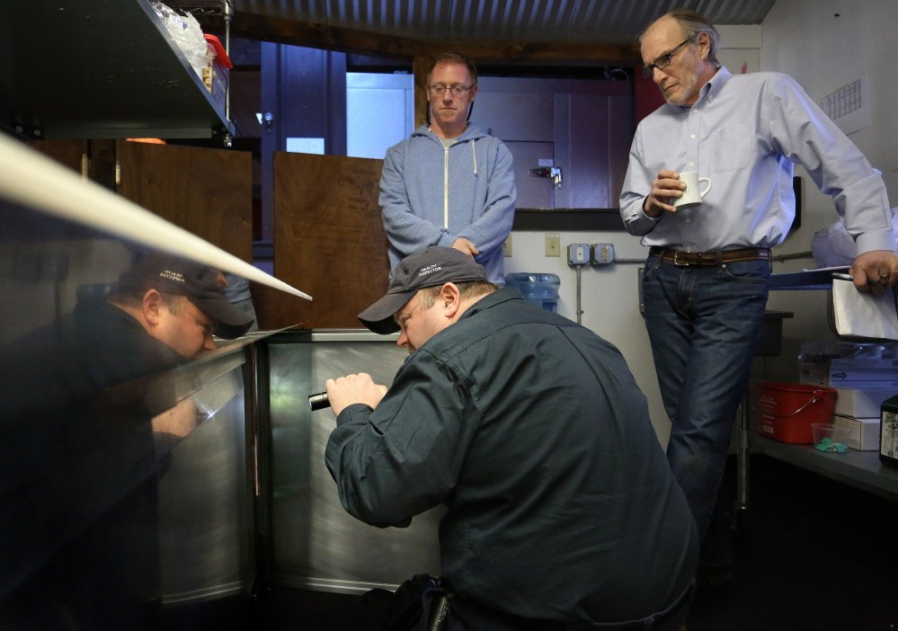Portland Health Inspector Tom Williams, front, inspects the kitchen of Buck's Naked BBQ on Wharf Street on Friday. Watching are restaurant owner Alex Caisse, left, and Al Brown, operations manager. Portland is one of just five communities allowed to conduct its own inspections.This caption was updated at 7 p.m. Sunday, Jan. 26, to correct the name of the owner of Buck's Naked BBQ.