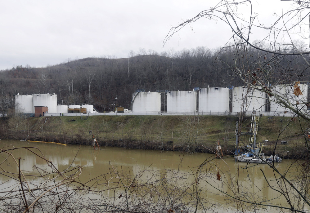 In this Monday, Jan. 13, 2014, file photo, workers,left, inspect an area outside a retaining wall around storage tanks where a chemical leaked into the Elk River at Freedom Industries storage facility in Charleston, W.Va.