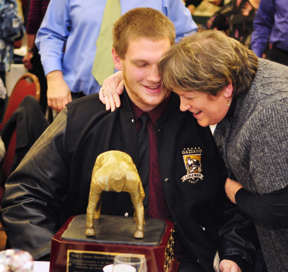 Staff photo by Joe Phelan Oak Hill defensive lineman Luke Washburn, left, gets a hug from his aunt Taffe Robbins after he won the Gaziano Lineman Award on Saturday January 25, 2014 in the Augusta Civic Center.