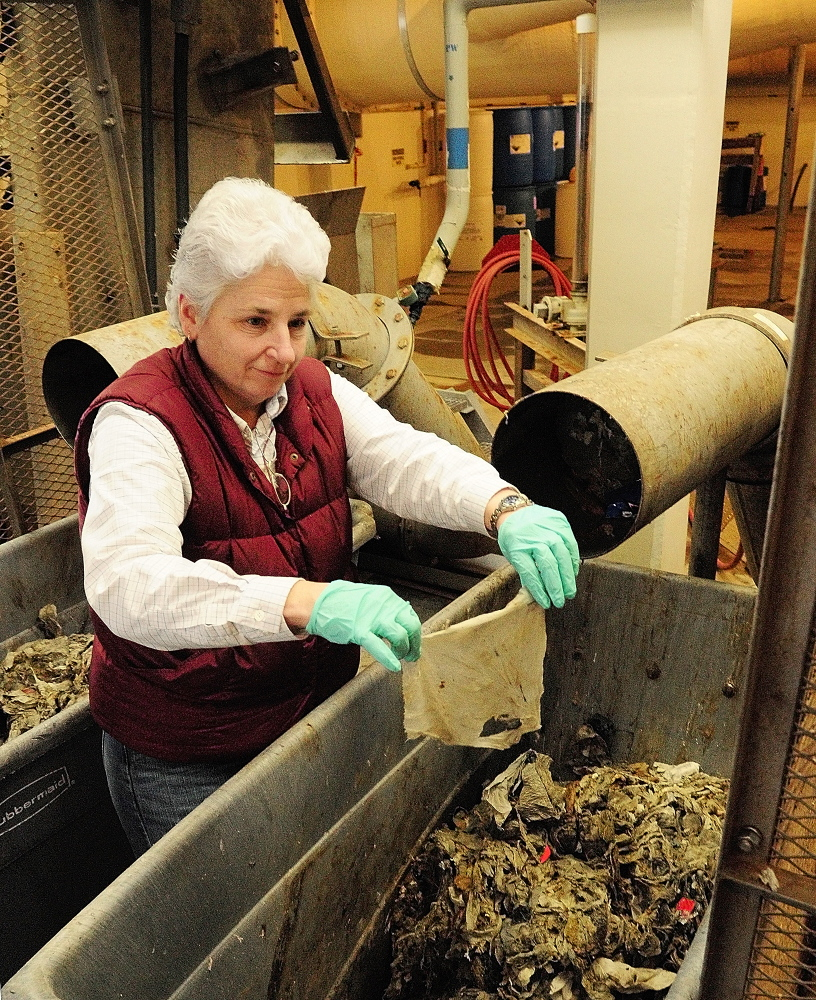Uninvited pest: Jane Carroll, process and safety director, pulls an intact baby wipe that came out of a rag press after it was removed by the bar rack at the beginning of the water treatment process Friday at the waste water treatment plant on Jackson Avenue in Augusta.
