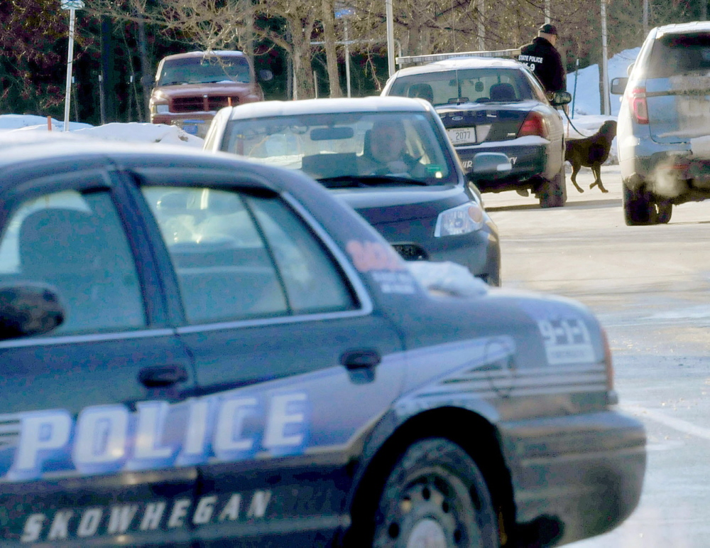 SEARCH: A police officer and a dog enter the Walmart store in Skowhegan shortly after a bomb threat was made on Tuesday.
