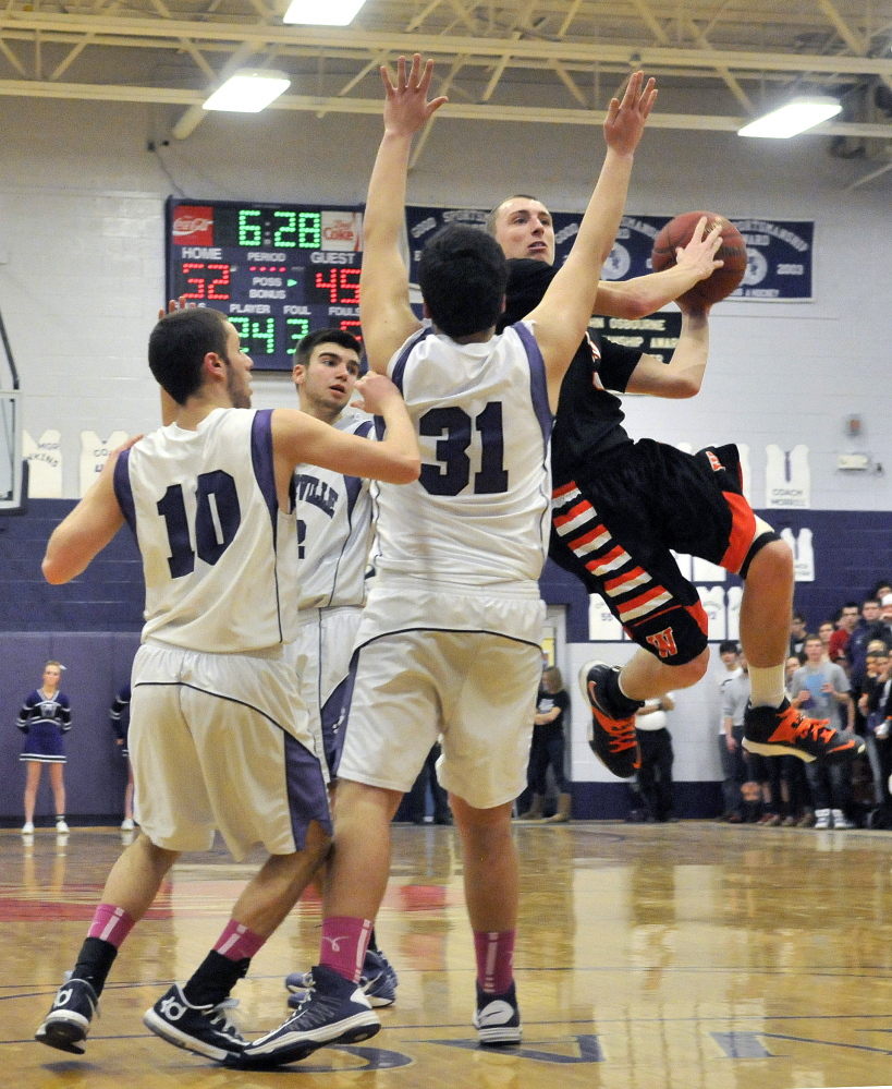 Staff photo by Michael G. Seamans Winslow High School's Trevor Lovely, 3, drives past Waterville Senior High School defenders in the fourth quarter in Waterville on Tuesday. Winslow defeated Waterville 59-54.
