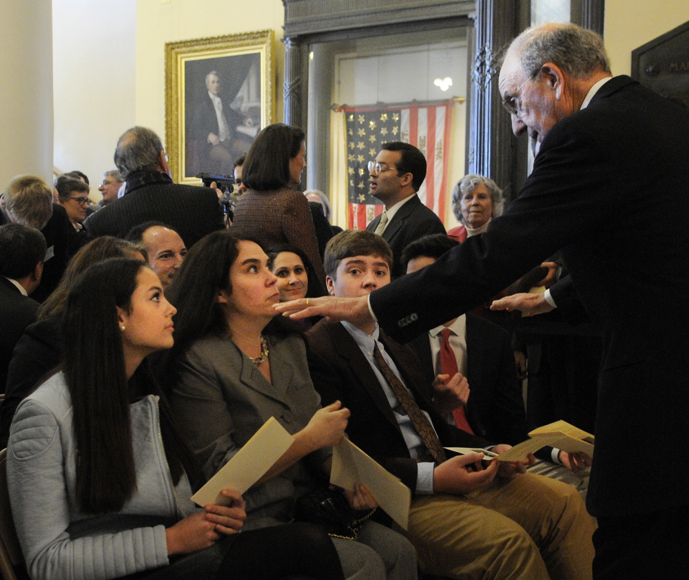 ON DISPLAY: Former US Senator George Mitchell speaks with his family Tuesday before the ceremony to unveil his official portrait at the Statehouse in Augusta. They are, seated from left, his daughter Claire, wife Heather, grandson Ian and son Andrew.