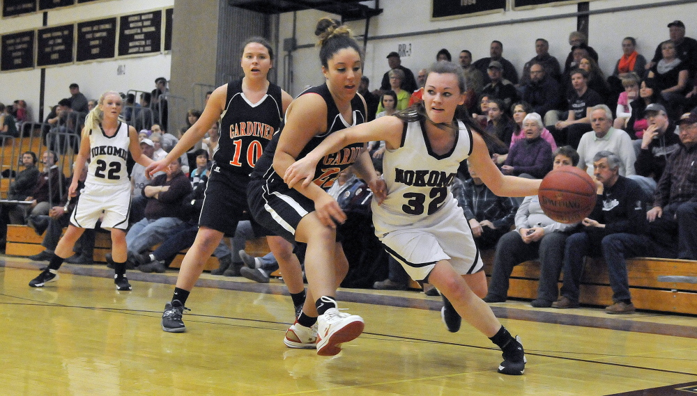 Staff photo by Michael G. Seamans Nokomis High School's Taylor Shaw, 32, drives the basket on Gardiner High School defender Savannah Vinton-Mullens, 22, in Newport on Wednesday.