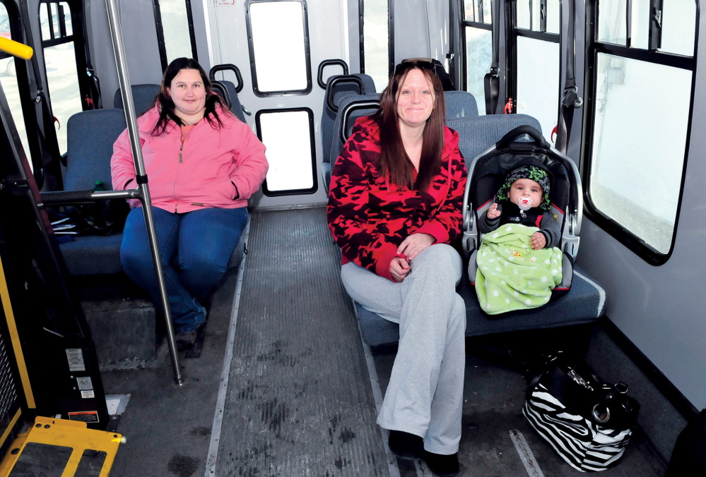 BUS STOPS HERE: Liza Dawes, left, of Madison and Star DeBerry and son Trigger of Skowhegan wait in a Somerset Explorer bus for more passengers Wednesday in the downtown municipal parking lot in Skowhegan. The bus service is getting a new bus shelter as part of the $400,000 revitalization of the parking lot.