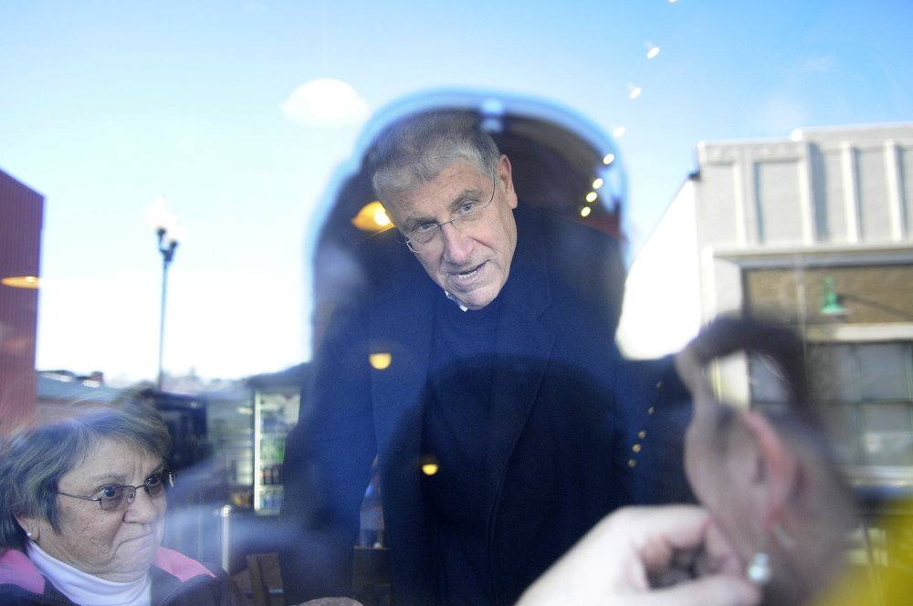 ON THE RUN: Viewed through the window of the Downtown Diner, on Water Street in Augusta, independent gubernatorial candidate Eliot Cutler speaks Wednesday with diners.