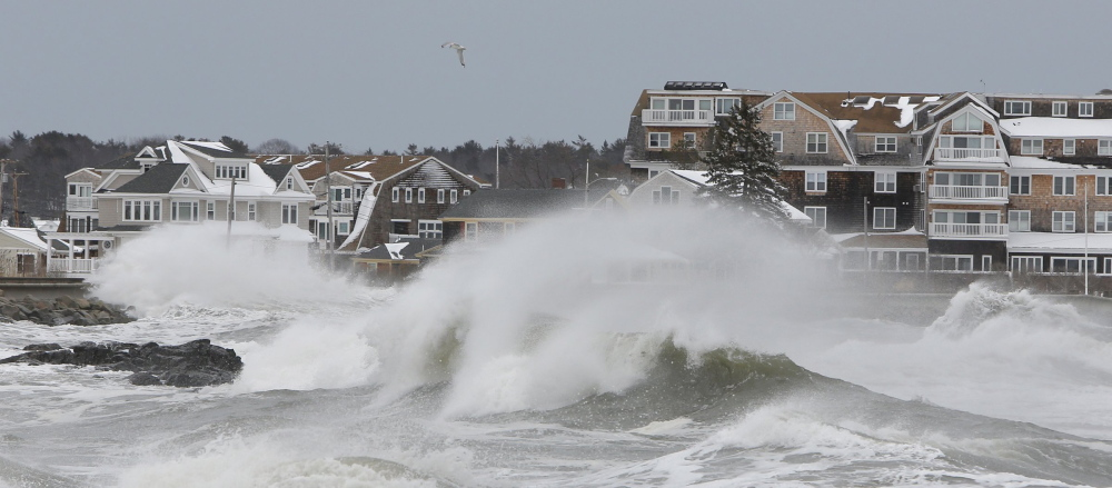 Large waves smash into a sea wall along the shore in Kennebunk last March. Some areas in York and Cumberland counties would be re-designated as at high risk for flooding under new federal flood maps.