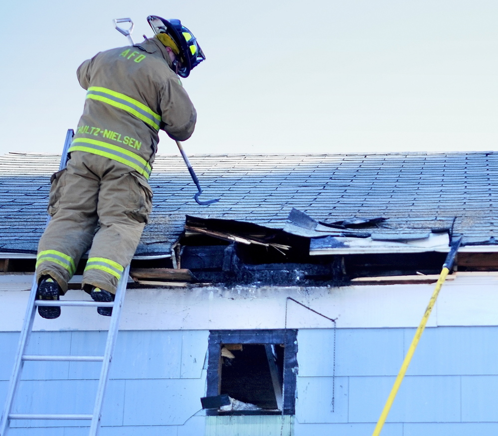 Thursday morning fire: Augusta firefighter Lars Schultz-Neilsen pulls down a section of burned garage roof on Brann Avenue in Augusta Thursday as he and other firefighters overhaul a fire-damaged garage to make sure there were no hot spots left.