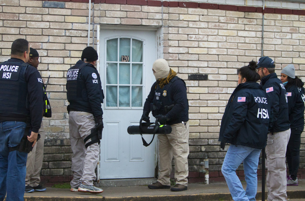 Federal agents prepare to enter a business during a raid, Thursday, Jan. 30, 2014, in southwest Houston. The raid was part of a crackdown on an alleged human smuggling ring operating in Texas and other states.