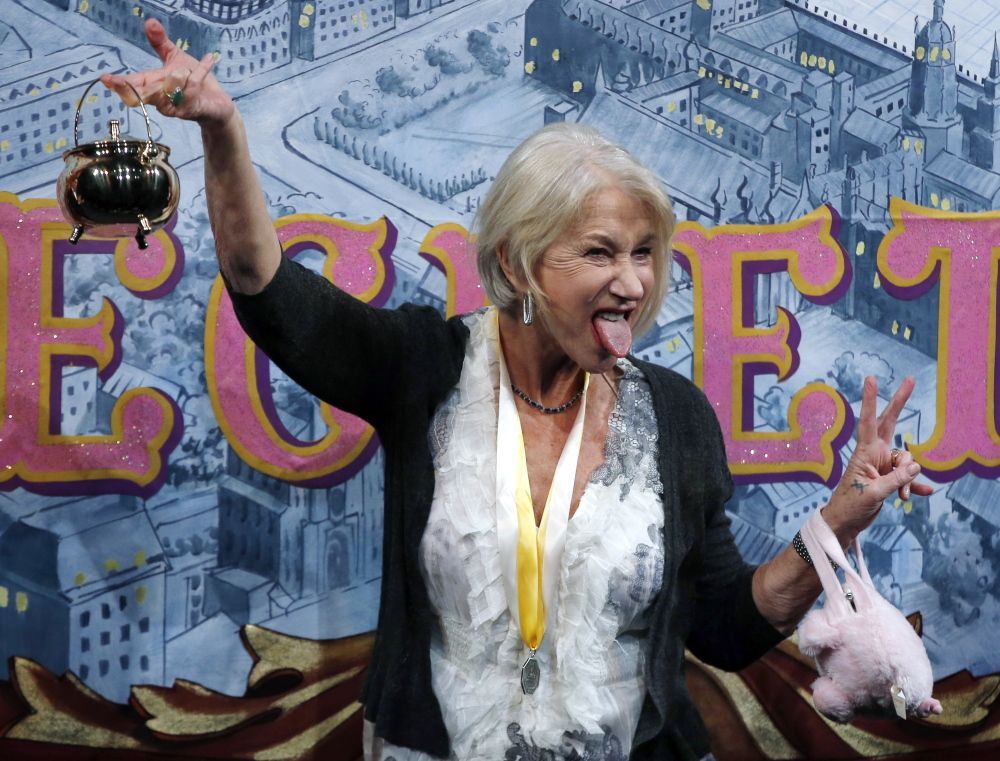 Actress Helen Mirren holds the Hasty Pudding Pot aloft during her roast as woman of the year by Harvard University's Hasty Pudding Theatricals in Cambridge, Mass., Thursday.