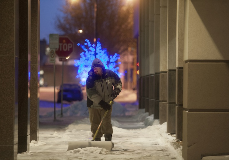 A worker clears the sidewalk at The Radisson Hotel in downtown Fargo, N.D., as temperatures of 20 degrees below zero and snow overnight brought out the shovels and snowblowers Monday, Jan. 27, 2014.The deep freeze that hit earlier this month has returned, bringing with it wind chills ranging from the negative teens to 40s, cancelations of schools, trains, flights and signs of resignation from parents forced to bring kids to work and residents who are tired of bundling up.