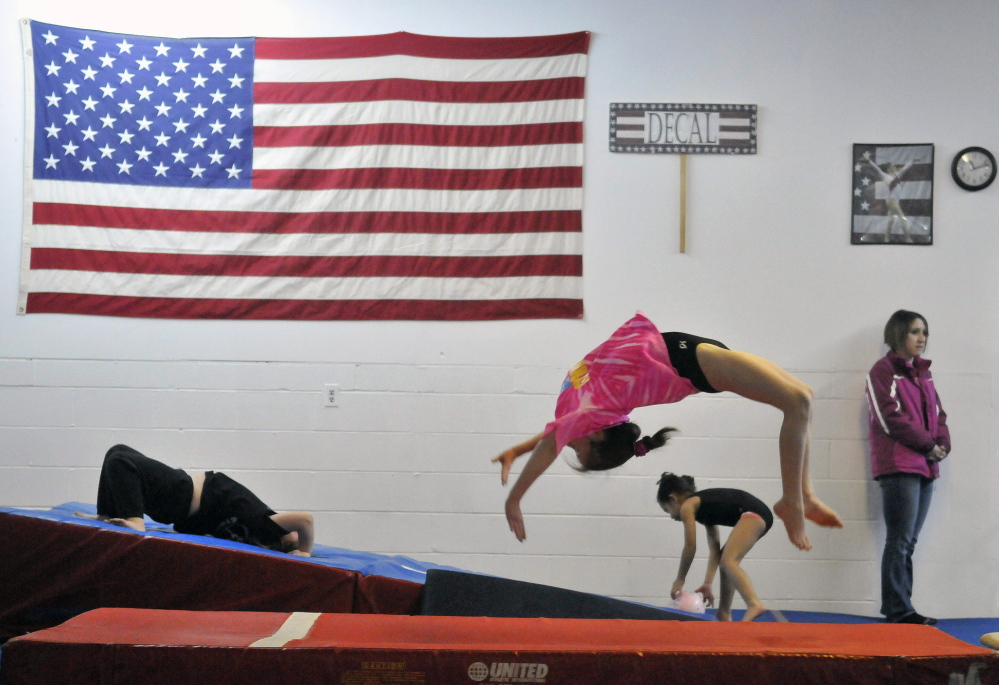 Glad to be back: Abby Drummond, 10, performs a back flip as she practices her vault routine at Decal Gymnastics in Farmington on Saturday. Decal re-opened today after closing because of flooding.