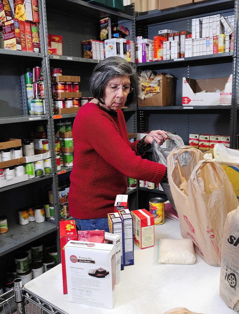 Helping out: Volunteer Elaine Brann, packs groceries for a client on Thursday at the Augusta Food Bank at St. Mark's Episcopal Church in Augusta.
