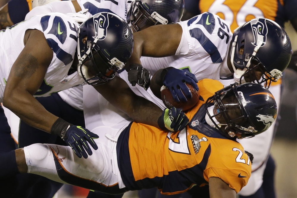 Denver Broncos' Knowshon Moreno is tackled by Seattle Seahawks' Chris Clemons, left, and Cliff Avril during the first half of the NFL Super Bowl XLVIII football game Sunday, Feb. 2, 2014, in East Rutherford, N.J.