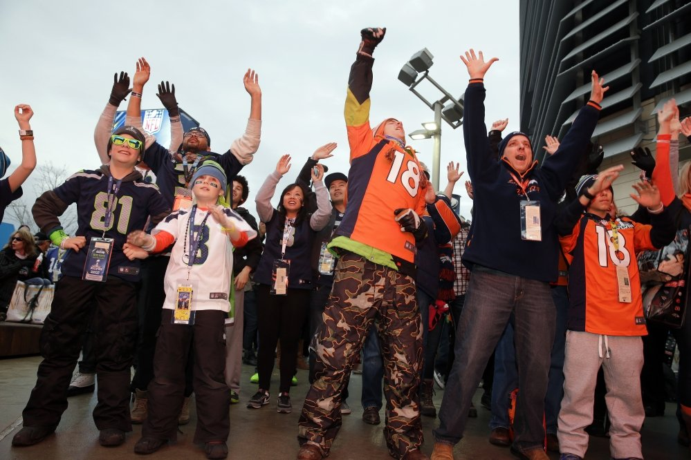 Fans play an interactive video game outside MetLife Stadium before the NFL Super Bowl XLVIII football game between the Seattle Seahawks and the Denver Broncos Sunday.
