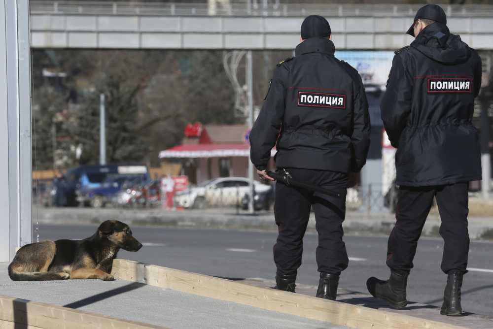 Policemen walk past a stray dog near the Media Center of the 2014 Winter Olympics on Monday in Krasnaya Polyana, Russia. Sochi authorities have hired a company to kill the packs of stray dogs to avoid Olympics embarrassment.