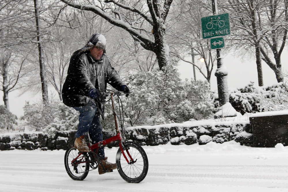 A cyclist makes his way up the Hudson River Greenway as heavy snow falls Monday in New York.