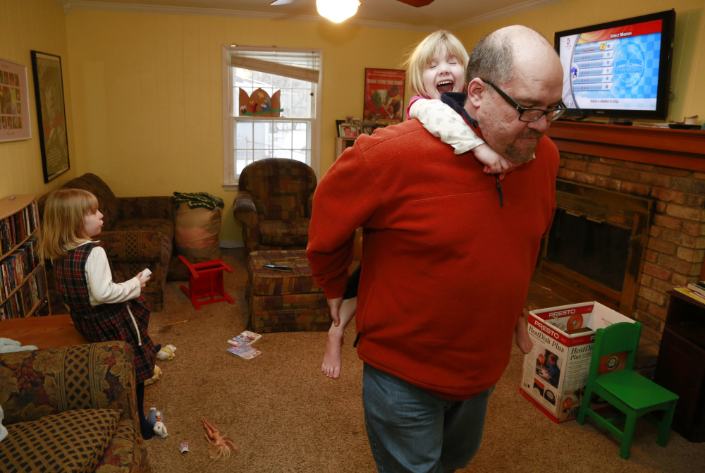 Mike Beck carries his daughter Veronica on his back through the living room as his daughter Maria, left, plays a video Monday.