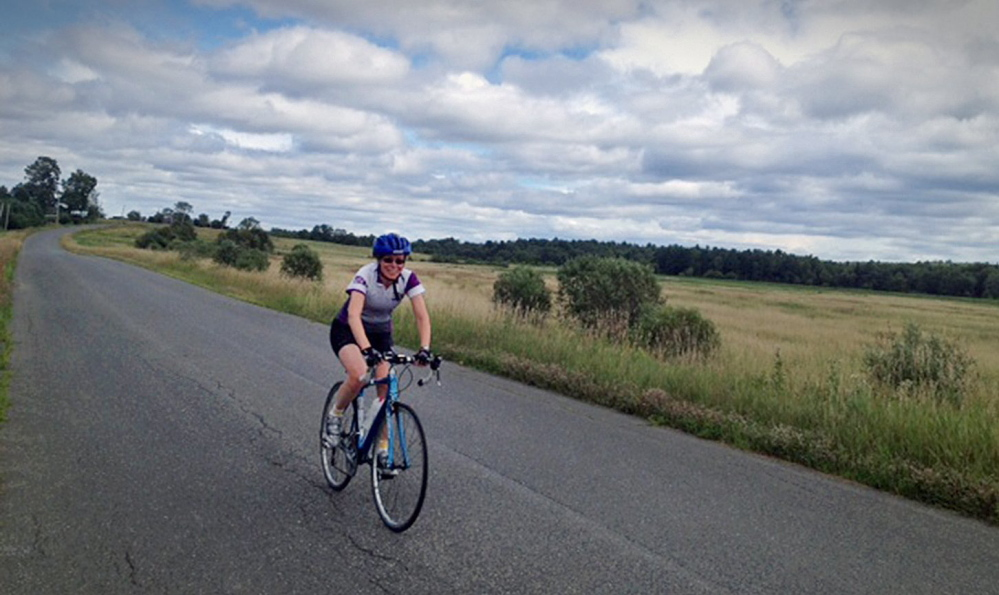 Kim True, ride director of the BikeMaine bicycle tour, rides along a stretch of last year's course in this August 2013 photo.