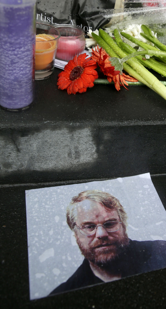 A makeshift memorial is seen Monday outside the New York building where the body of Philip Seymour Hoffman was found.