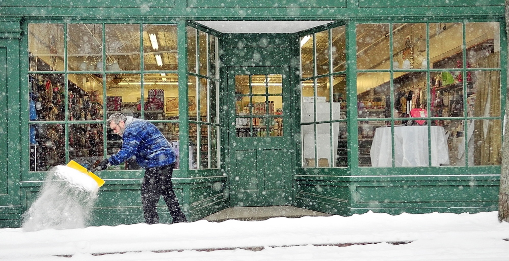 As more snow continues to fall, store manager Dennis Trimpop shovels on Wednesday in front of Reny's Department Store on Water Street in Gardiner.